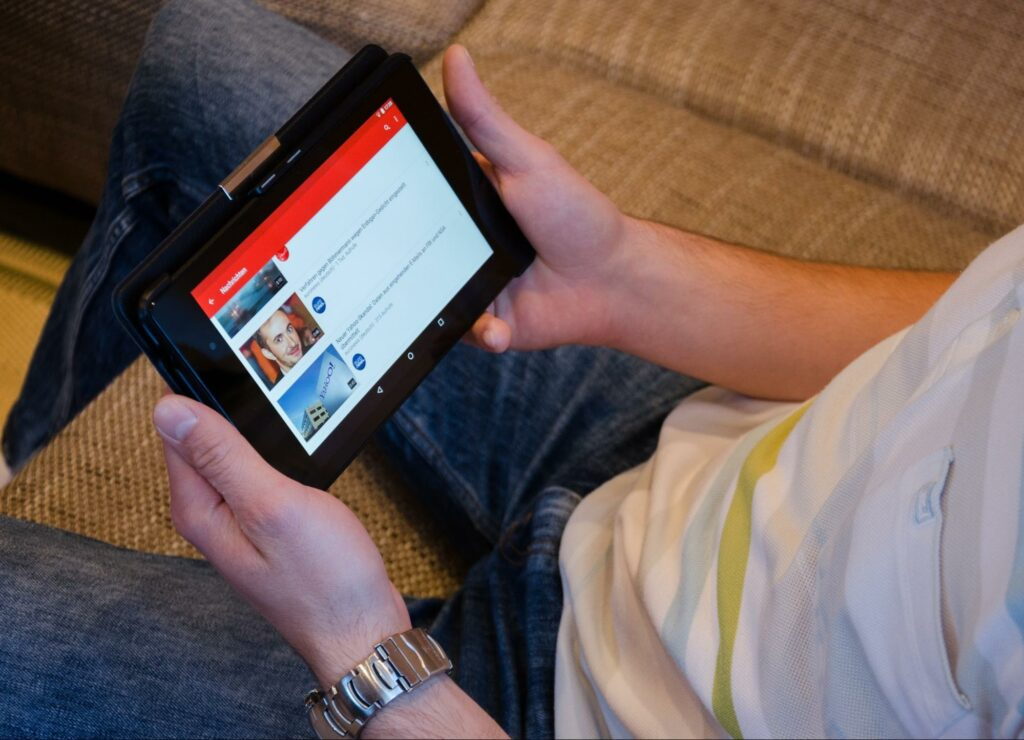 Person looking at YouTube videos on a tablet, shows that media embedded in a website can cause problems for people with disabilities