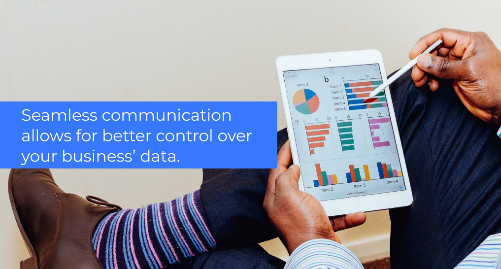 Someone looking at data on a tablet with text: Seamless communication allows for better control over your business' data.