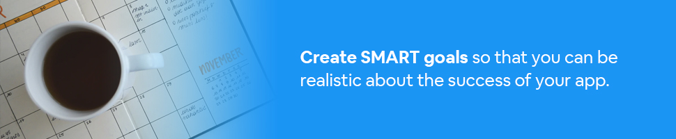 A coffee cup on a monthly goal calendar with text: Create SMART goals so that you can be realistic about the success of your app.