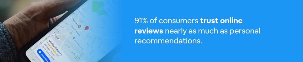 A person looking at an online review on Google Maps with text: 91% of consumers trust online reviews nearly as much as personal recommendations.