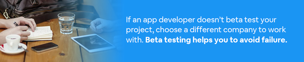 Someone taking notes with a mobile app and tablets on a table with text: If an app developer doesn't beta test your project, choose a different company to work with. Beta testing helps you to avoid failure.