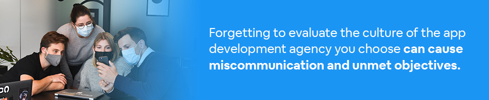 Team members at an app development agency looking at a smartphone with text: Forgetting to evaluate the culture of the app development agency you choose can cause miscommunication and unmet objectives.